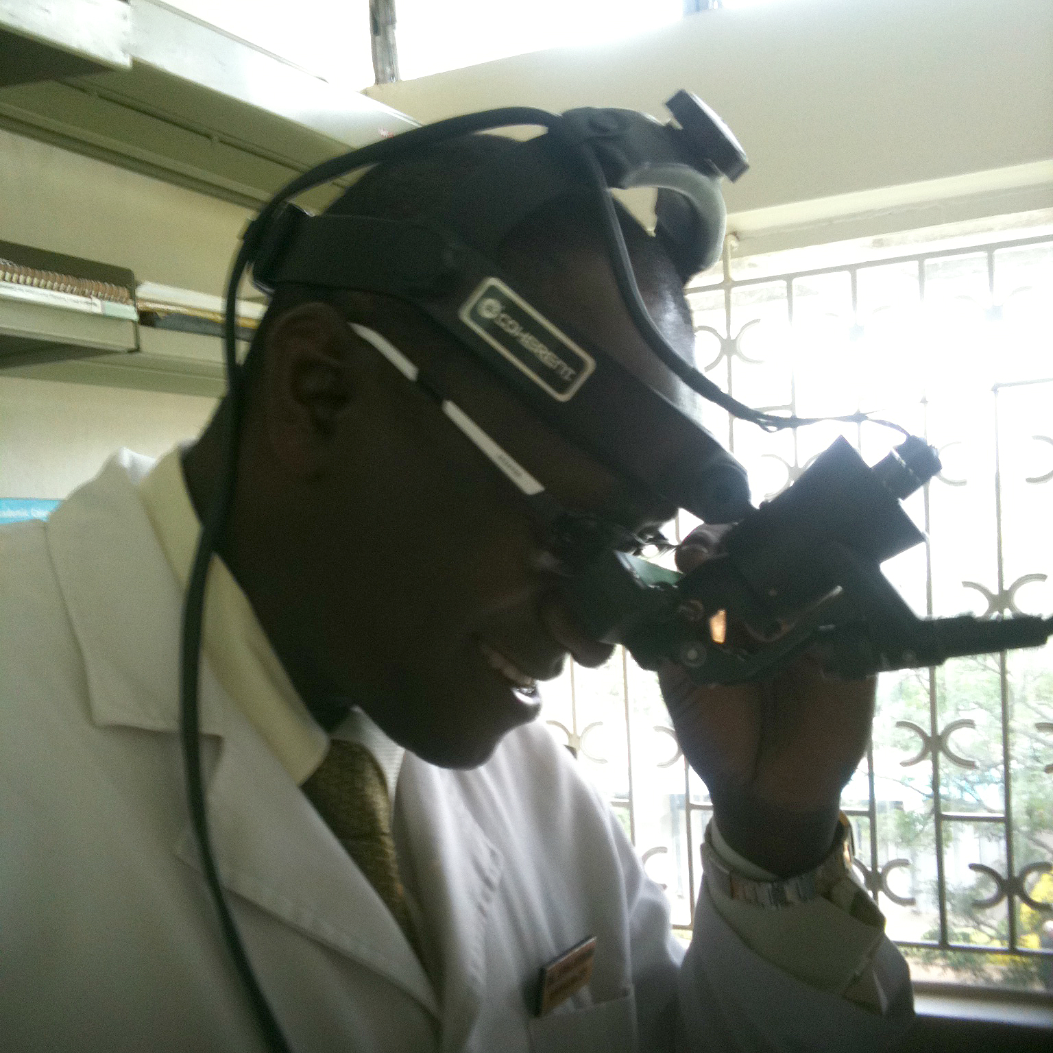 Photo of Dr. Abba Hydara, using an indirect ophthalmoscope