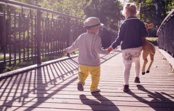 Image of children holding hands and walking across a bridge.