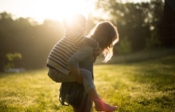 Image of siblings piggybacking on each other in the park.