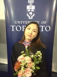 Anita Yin holding flowers at University of Toronto graduation