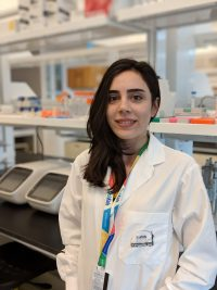 Bahareh Adhami-Mojarad wearing labcoat with lab bench in background