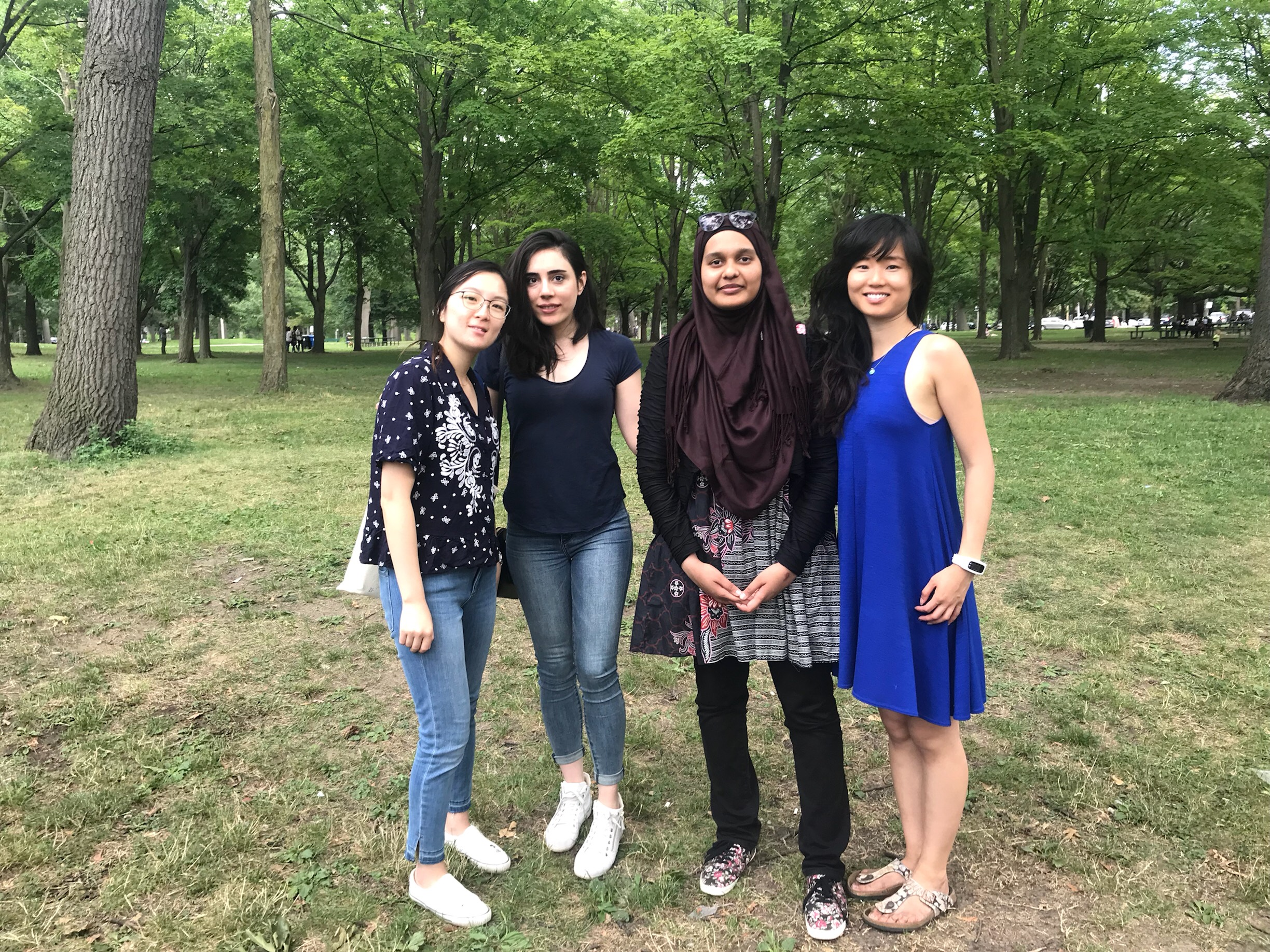 4 women (Anita, Bahareh, Farah, and Jacqueline) looking at the camera standing on grass with trees in the background