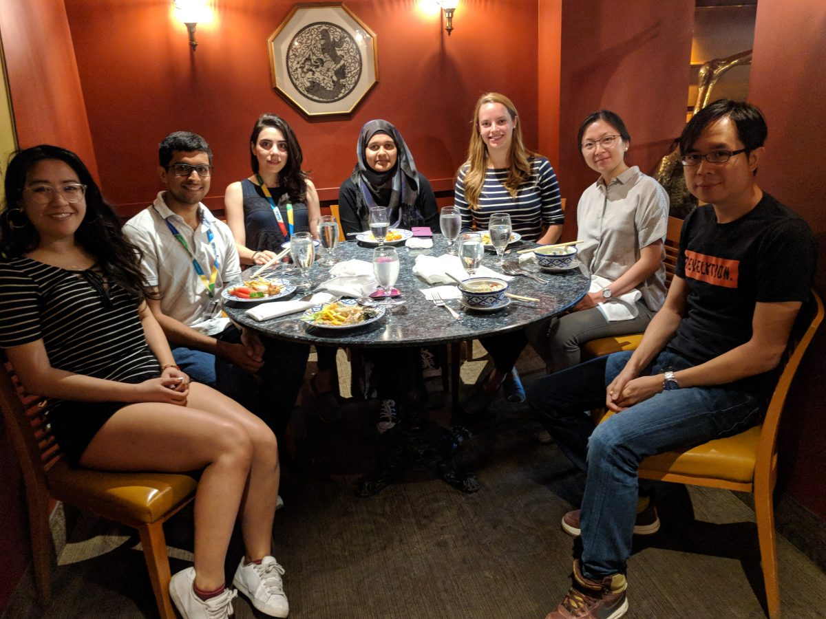 7 people smiling at the camera seated around a grey round table with food