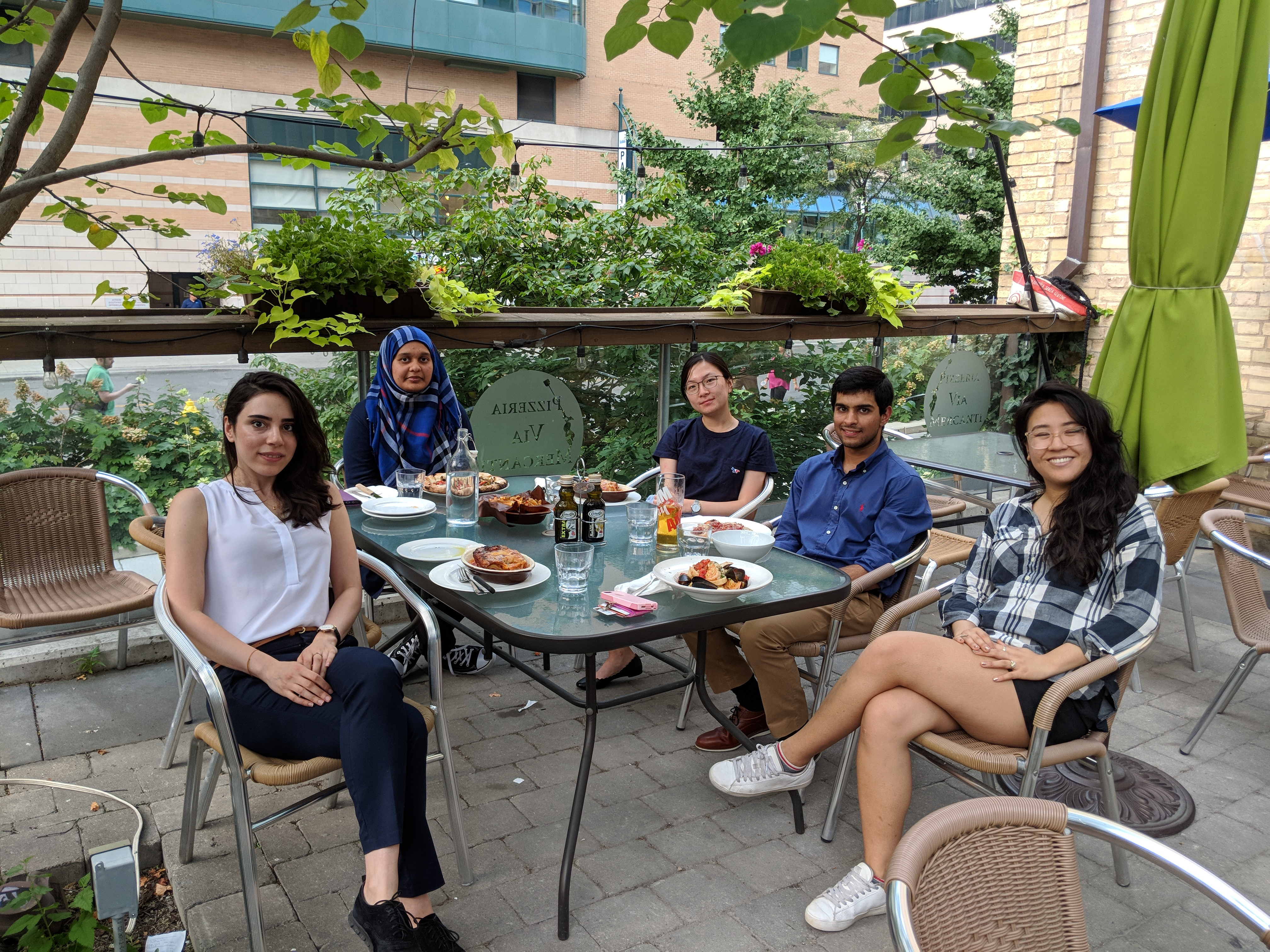 5 lab members sitting around an outdoor patio table with food