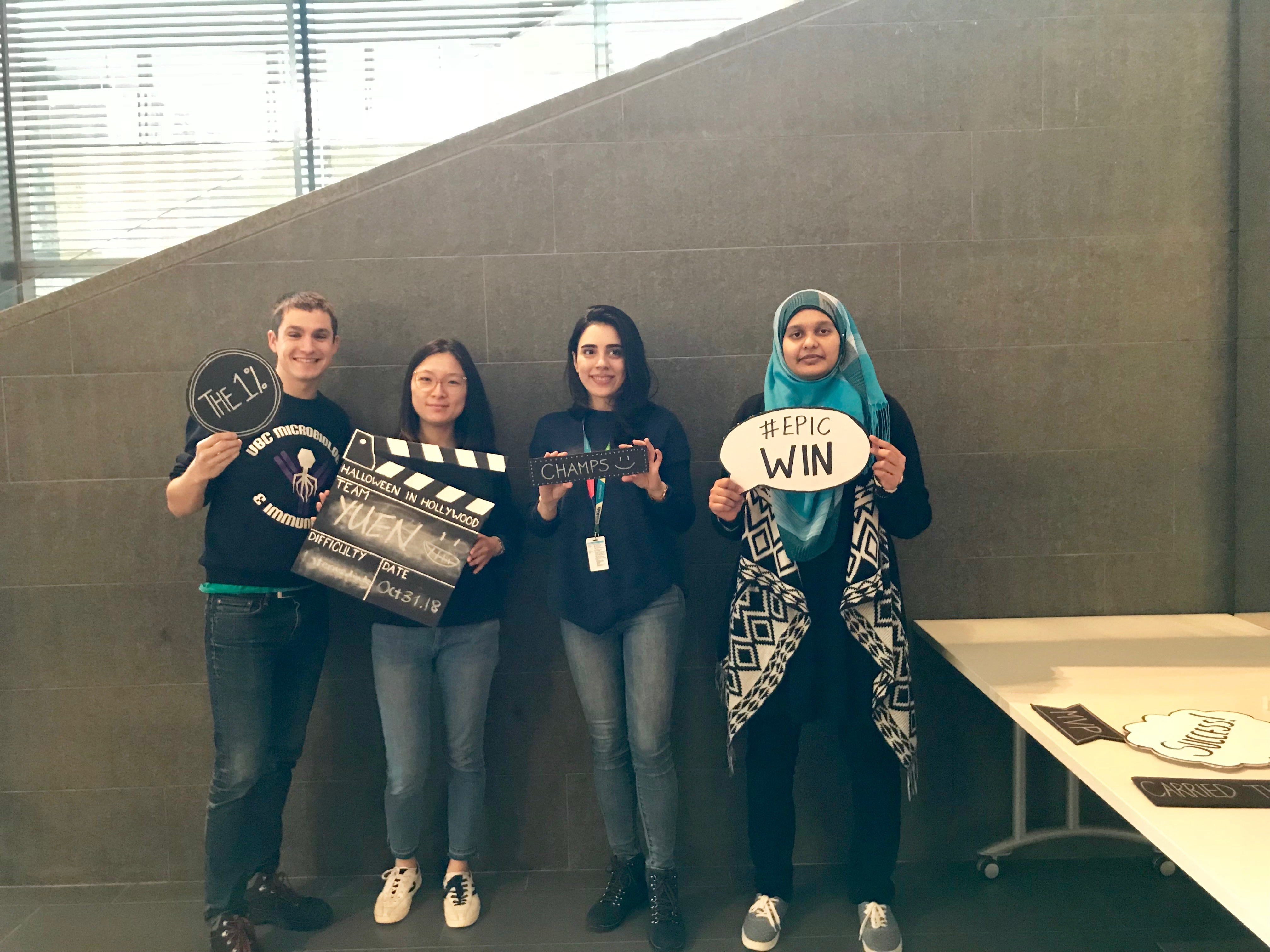 4 lab members holding up signs about completing an escape room challenge